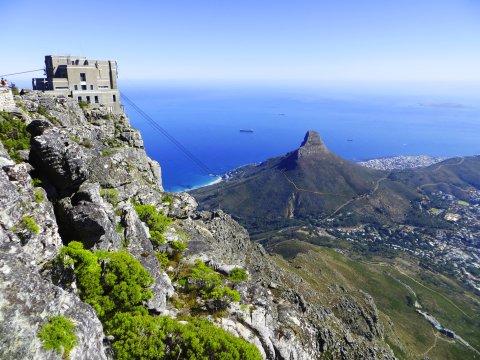 Suedafrika Kapstadt Blick vom Tafelberg auf Seilbahnstation und Lions Head