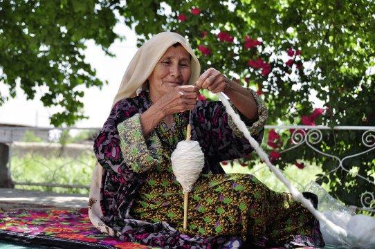 Usbekin beim traditionellen Spinnen von Garn