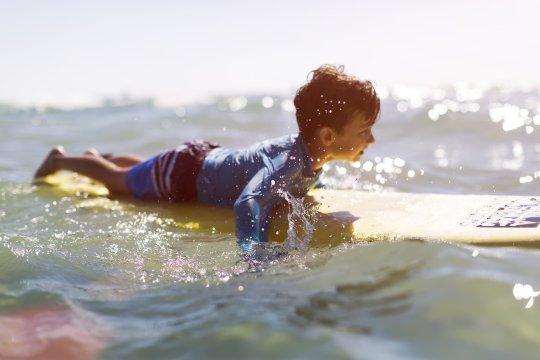 Kind auf Surfbrett